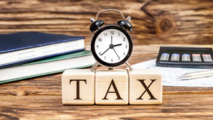 Word-Tax-with-clock-on-the-office-workplace.-Business-concept
